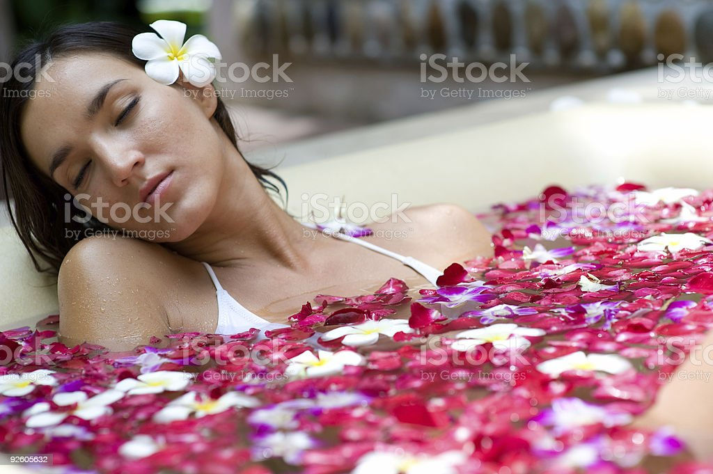 A beautiful woman relaxing in a bath with flowers stock photo