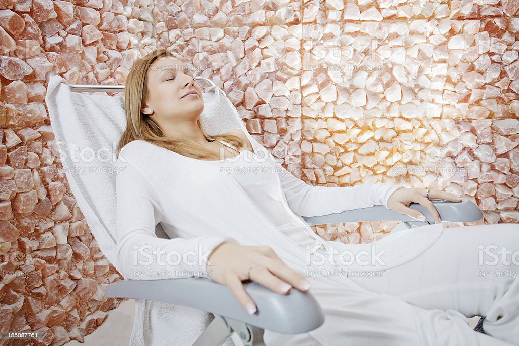 Beautiful woman relaxing in salt room. stock photo