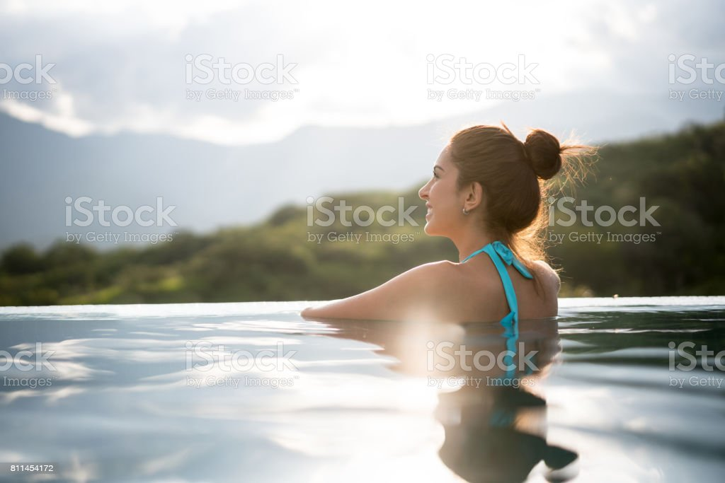 Beautiful woman relaxing in the pool stock photo