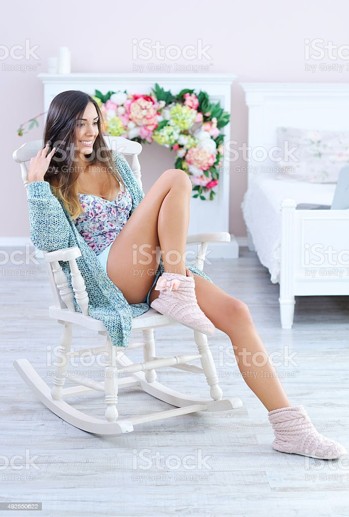 Beautiful woman relaxing in white rocking chair stock photo