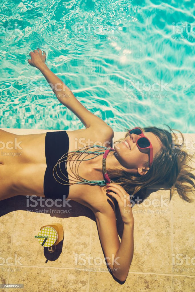 Beautiful woman relaxing on the pool. stock photo