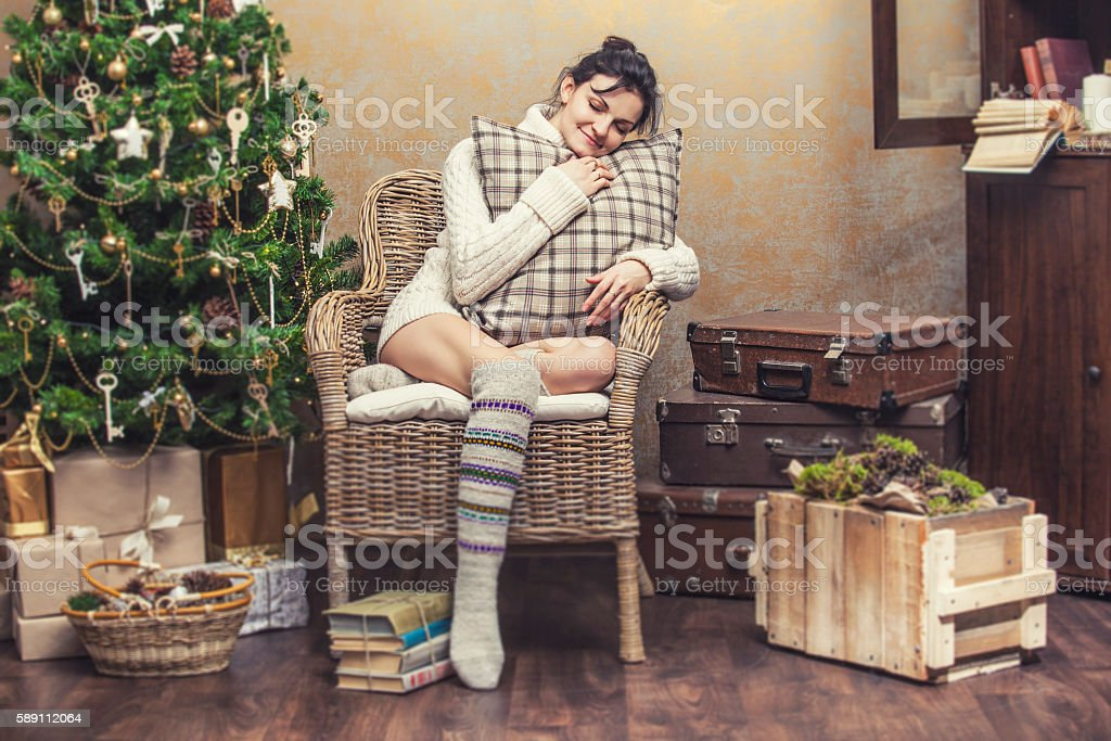 Beautiful woman relaxing sitting in a chair in the Christmas stock photo
