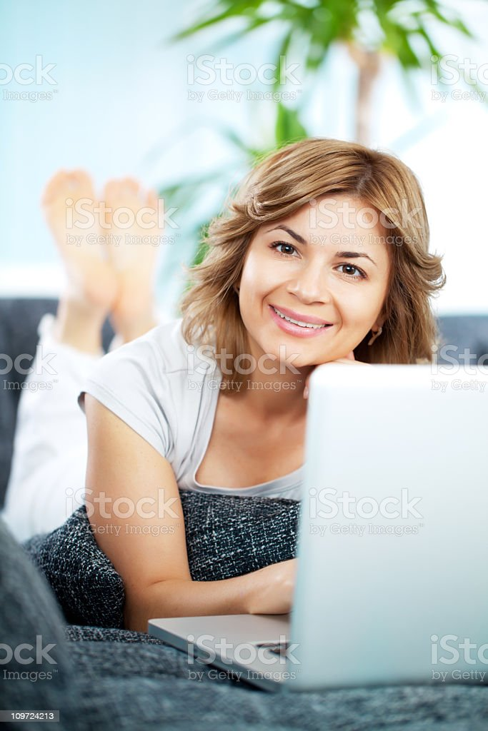 Beautiful woman resting at home, using laptop computer. royalty-free stock photo