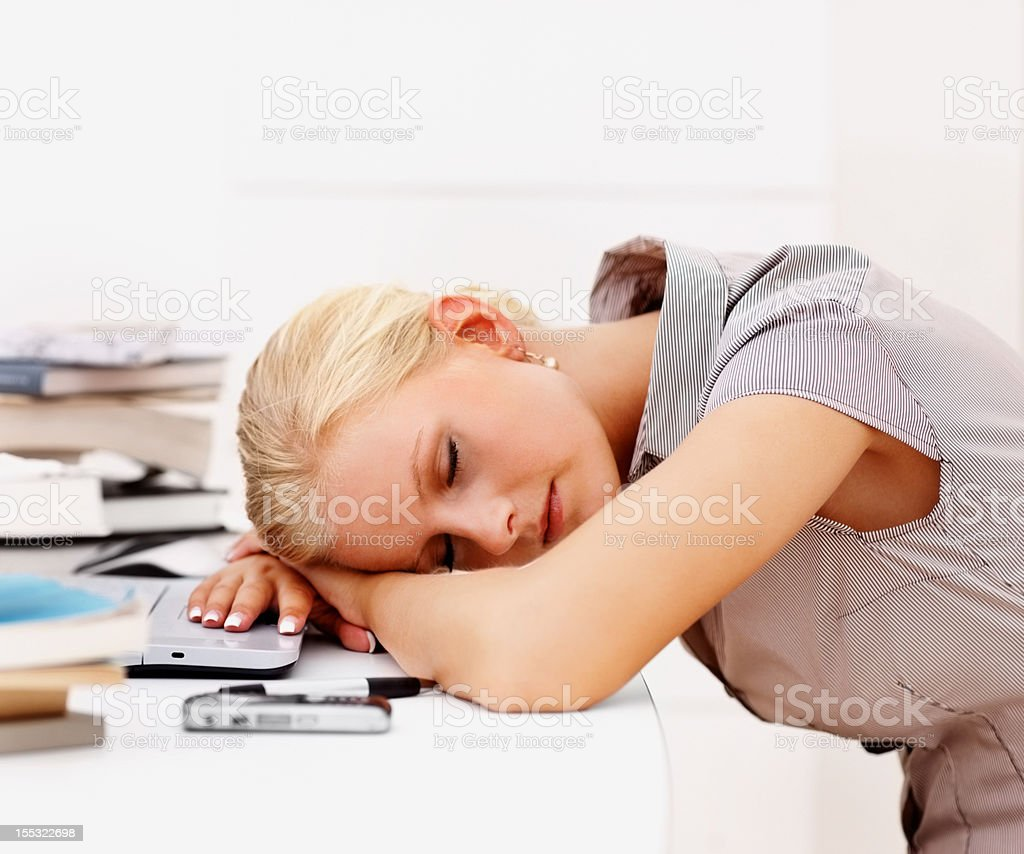 Beautiful woman resting head on table while studying royalty-free stock photo