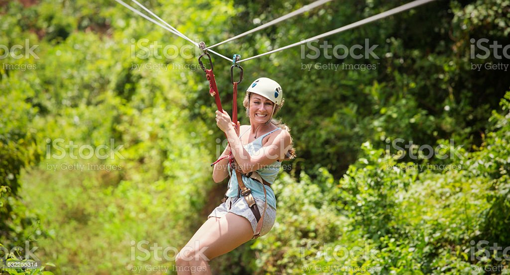 Beautiful woman riding a zip line in a lush tropical forest stock photo