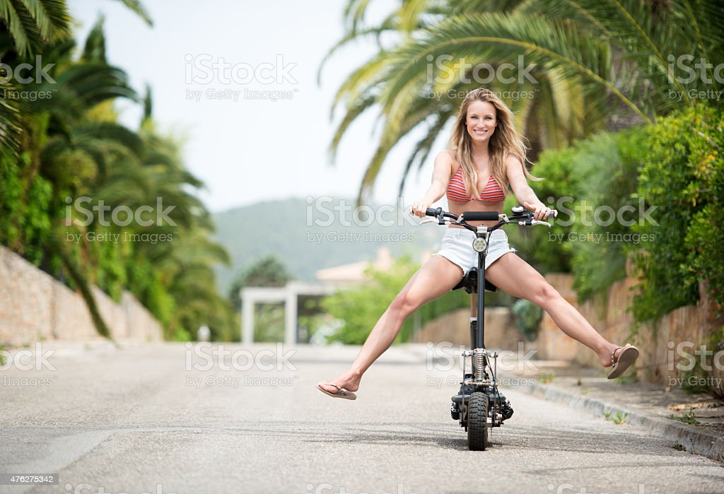 Beautiful woman riding an Electric Scooter stock photo