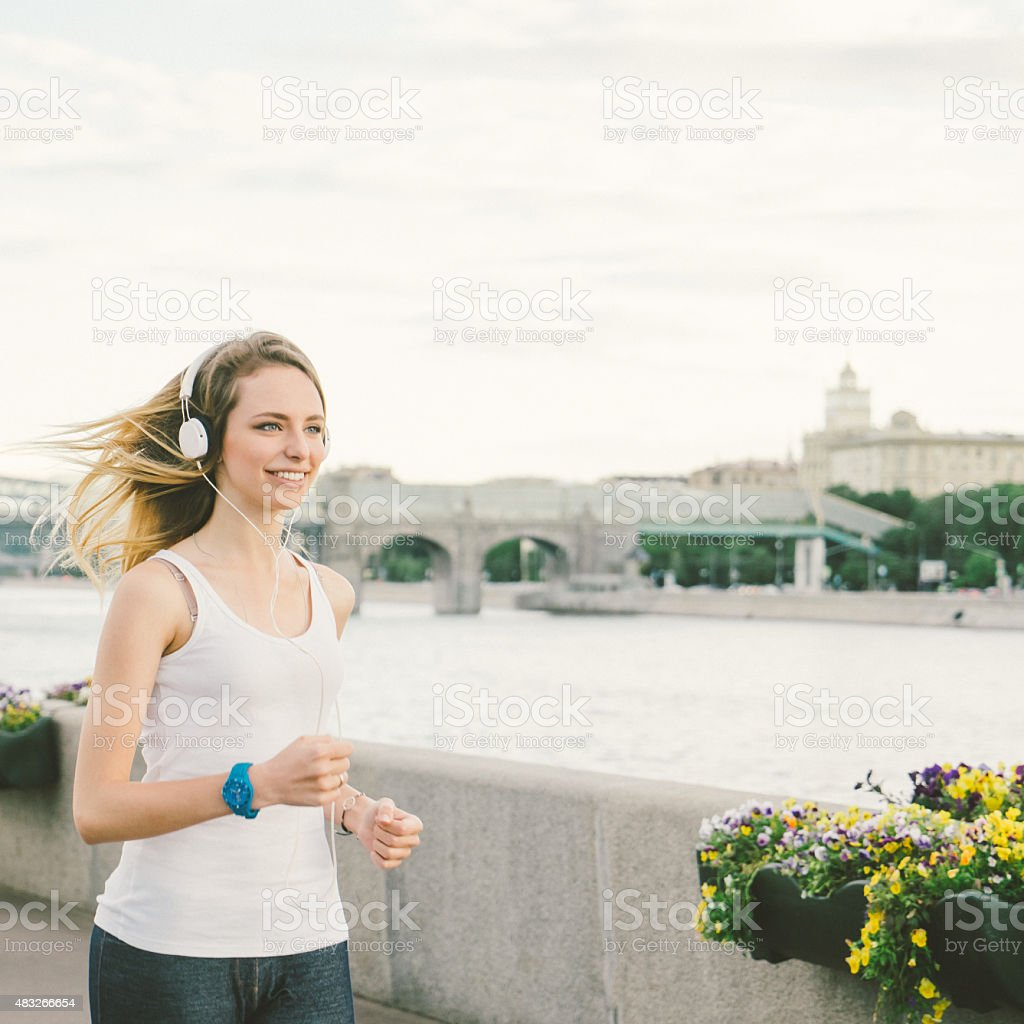 Beautiful Woman Running And Listening To Her Favorite Music stock photo