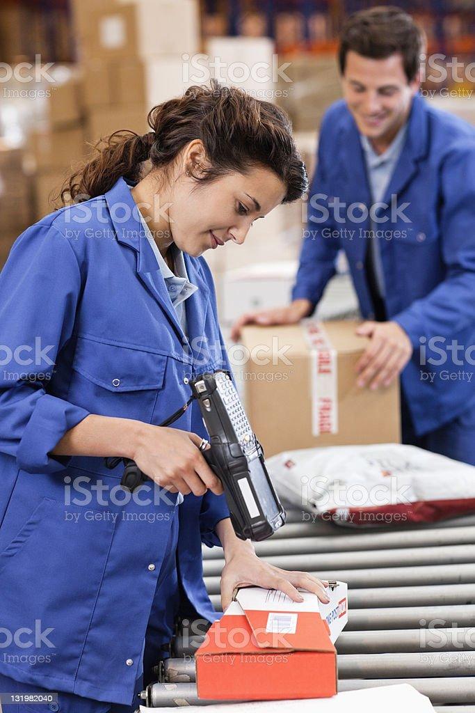 Beautiful woman scanning barcodes on conveyor belt royalty-free stock photo