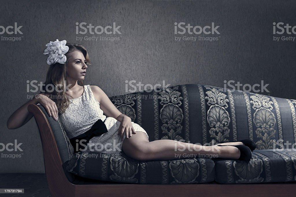 Beautiful woman seated on a sofa royalty-free stock photo