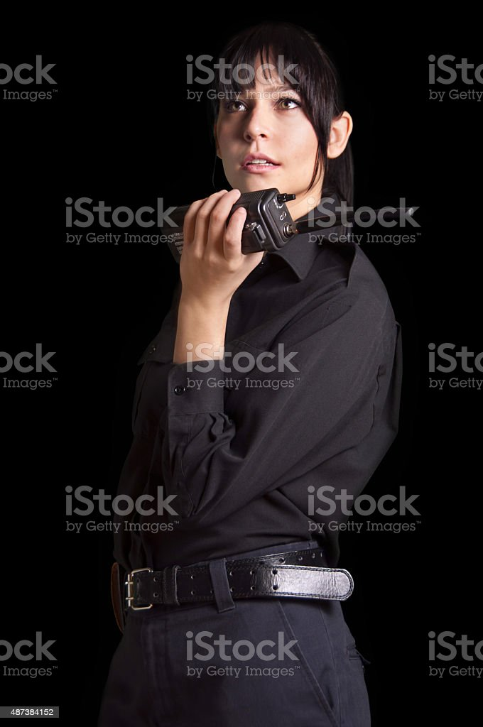 Beautiful woman security Police Officer Holding a Walkie-talkie black background stock photo