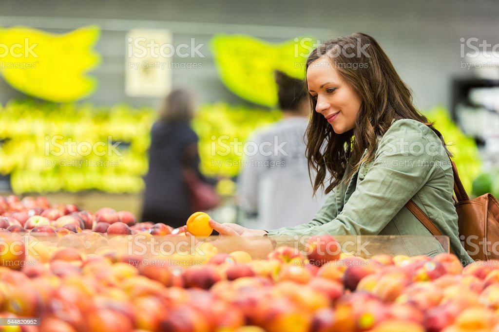 Beautiful woman shops for fruit in market stock photo