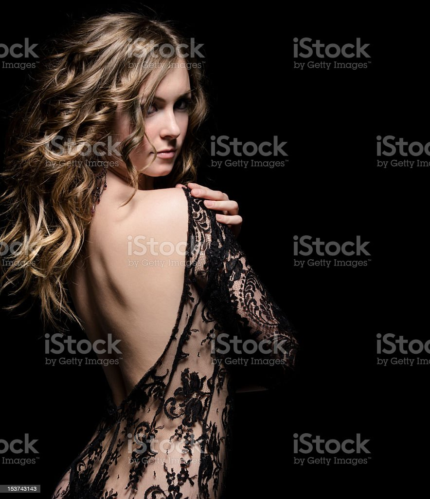 Beautiful woman showing back in laced dress stock photo