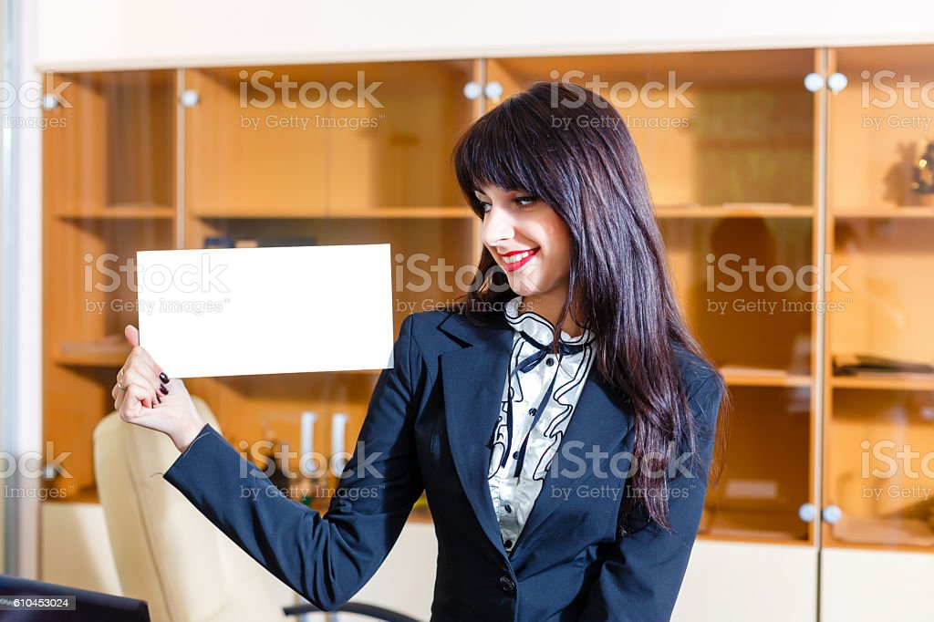 Beautiful woman showing empty card in office stock photo