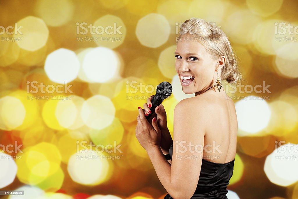 Beautiful woman singing into a microphone royalty-free stock photo