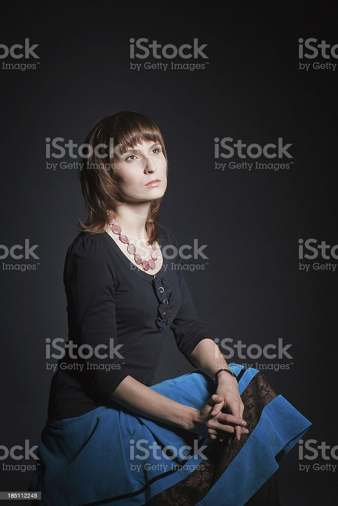 Beautiful woman sitting against black background stock photo