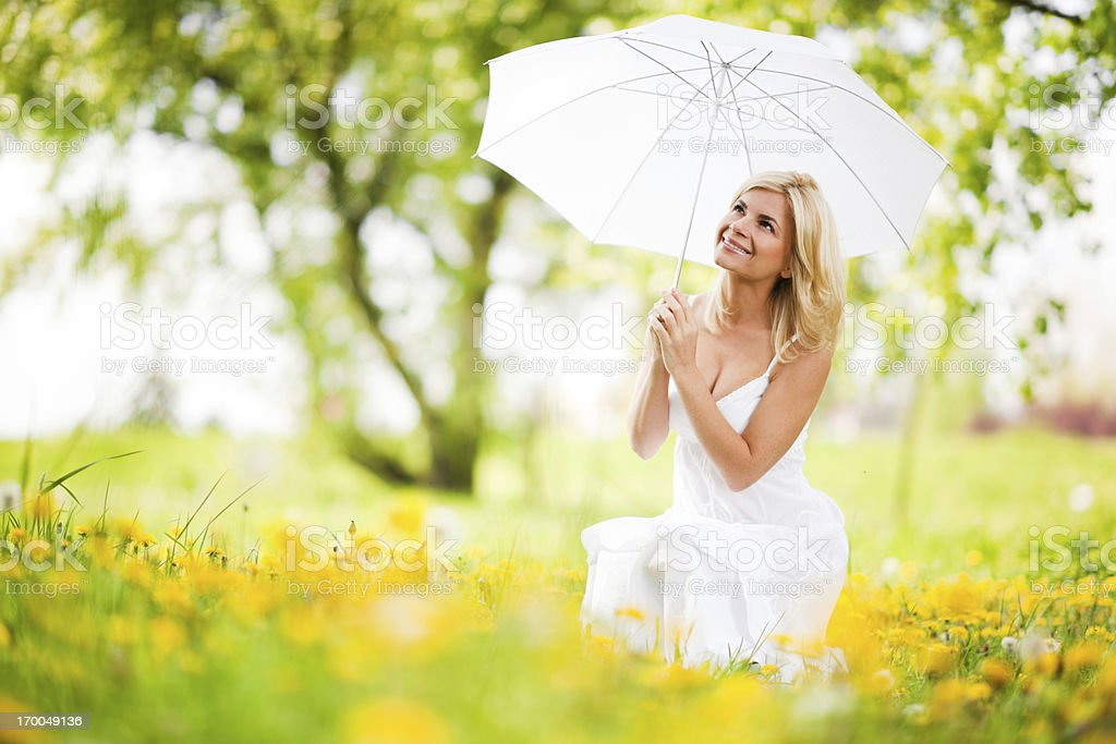 Beautiful woman sitting among flowers and holding umbrella. royalty-free stock photo