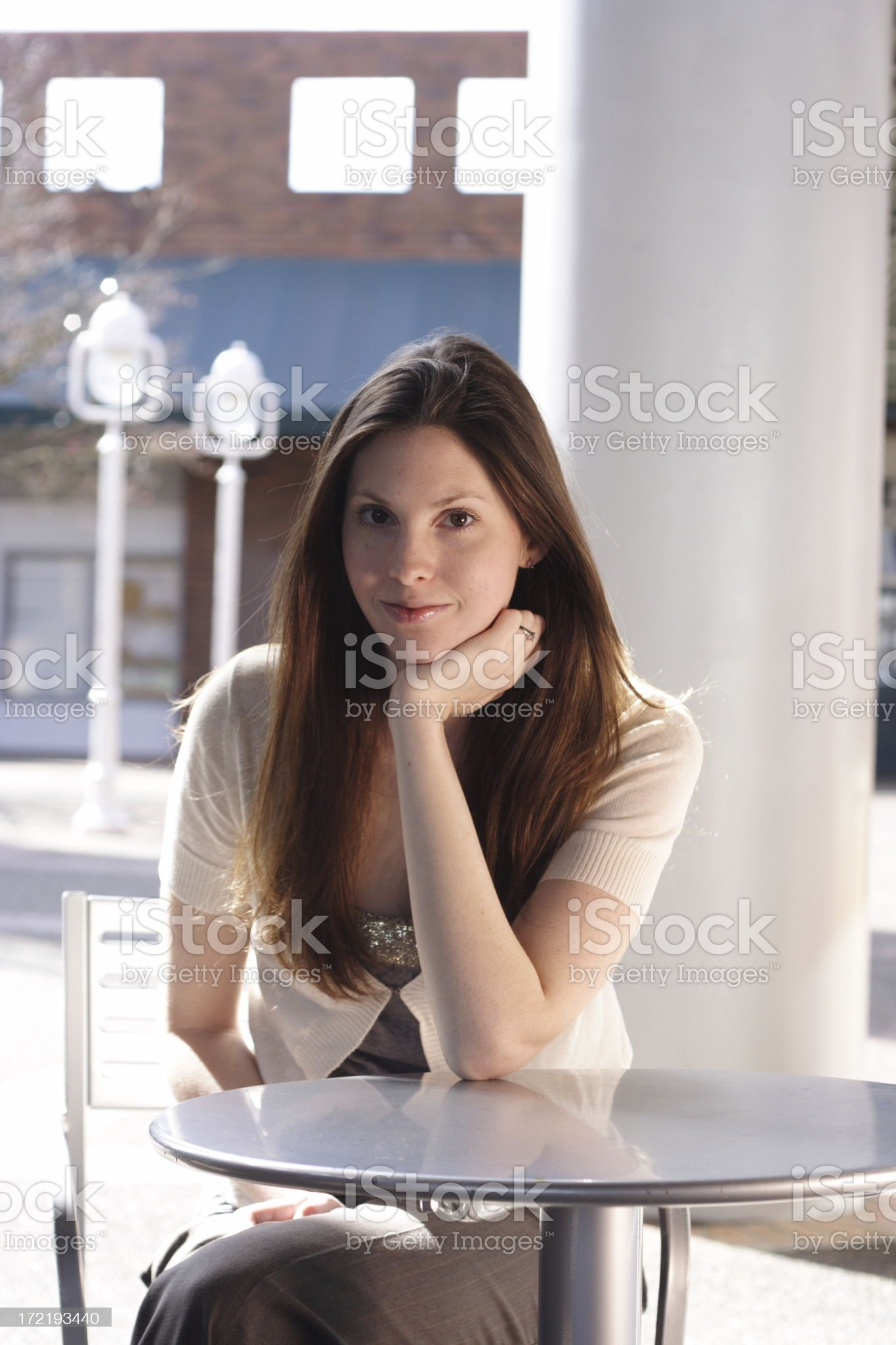 beautiful woman sitting at a cafe table royalty-free stock photo