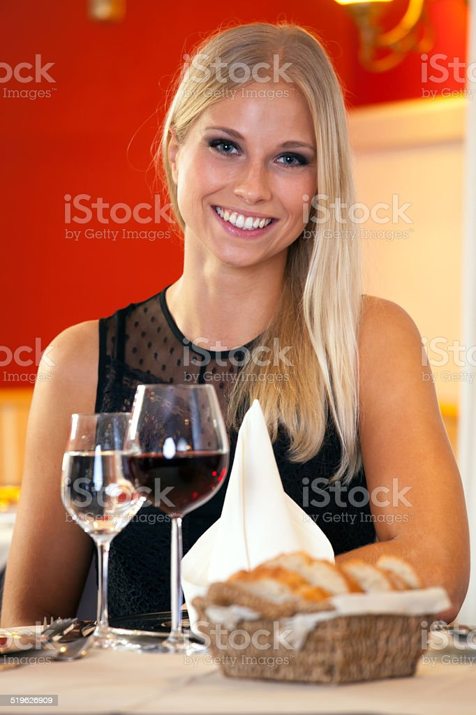 Beautiful woman sitting at table in a restaurant. stock photo