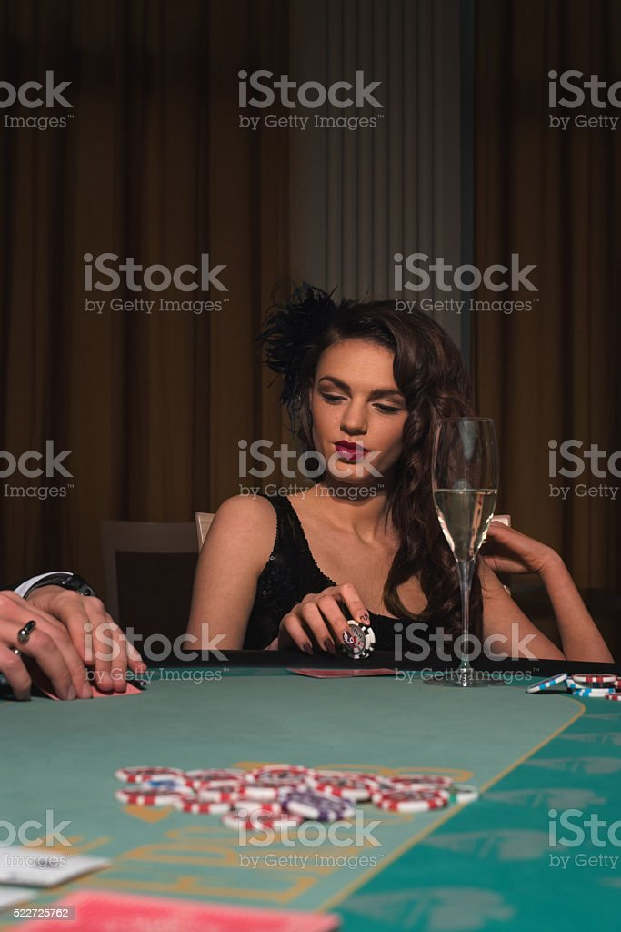 Beautiful woman sitting at the poker table stock photo
