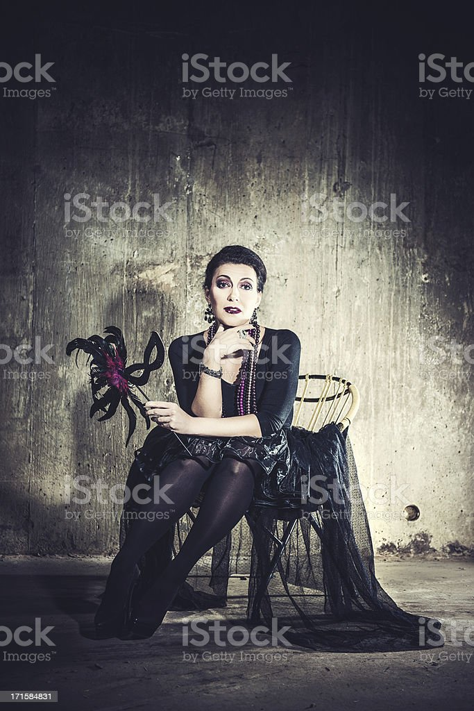 Beautiful woman sitting in a basement stock photo