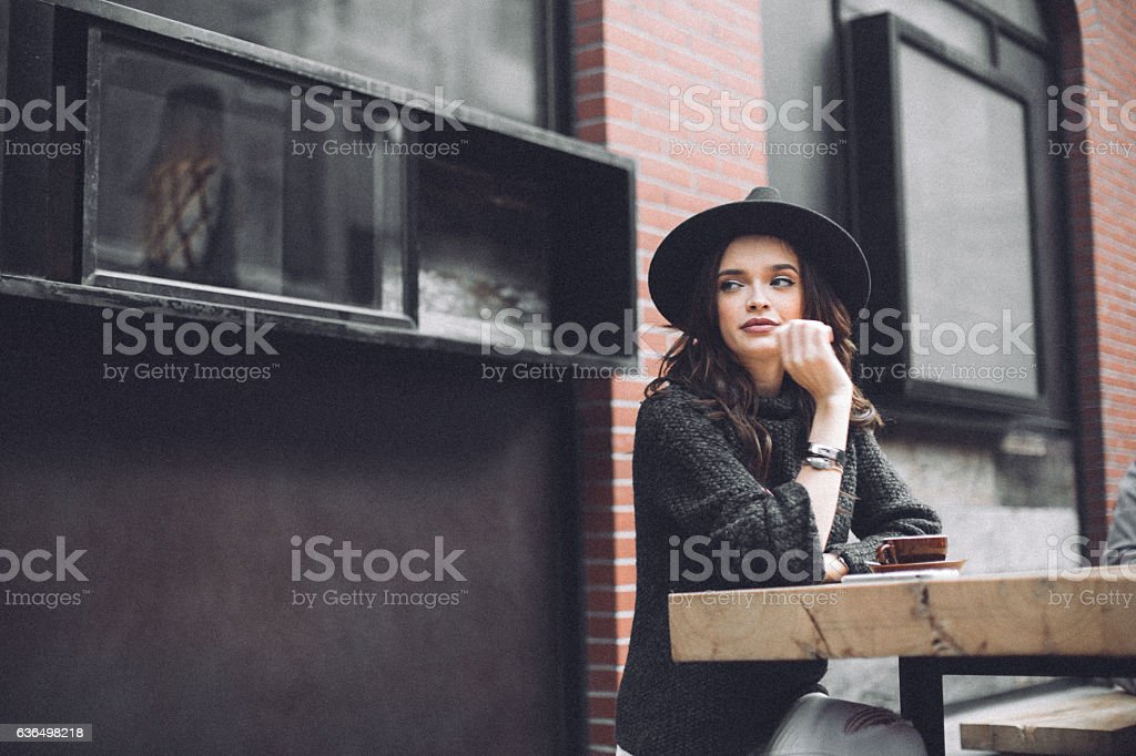 Beautiful woman sitting in a cafe alone stock photo