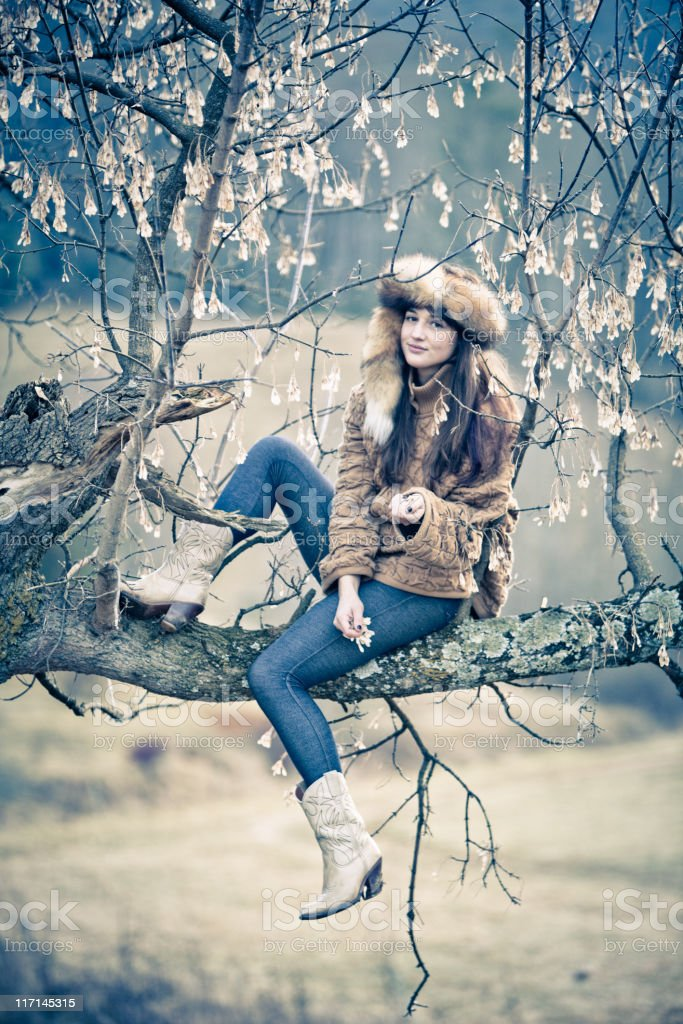 Beautiful woman sitting in a tree royalty-free stock photo