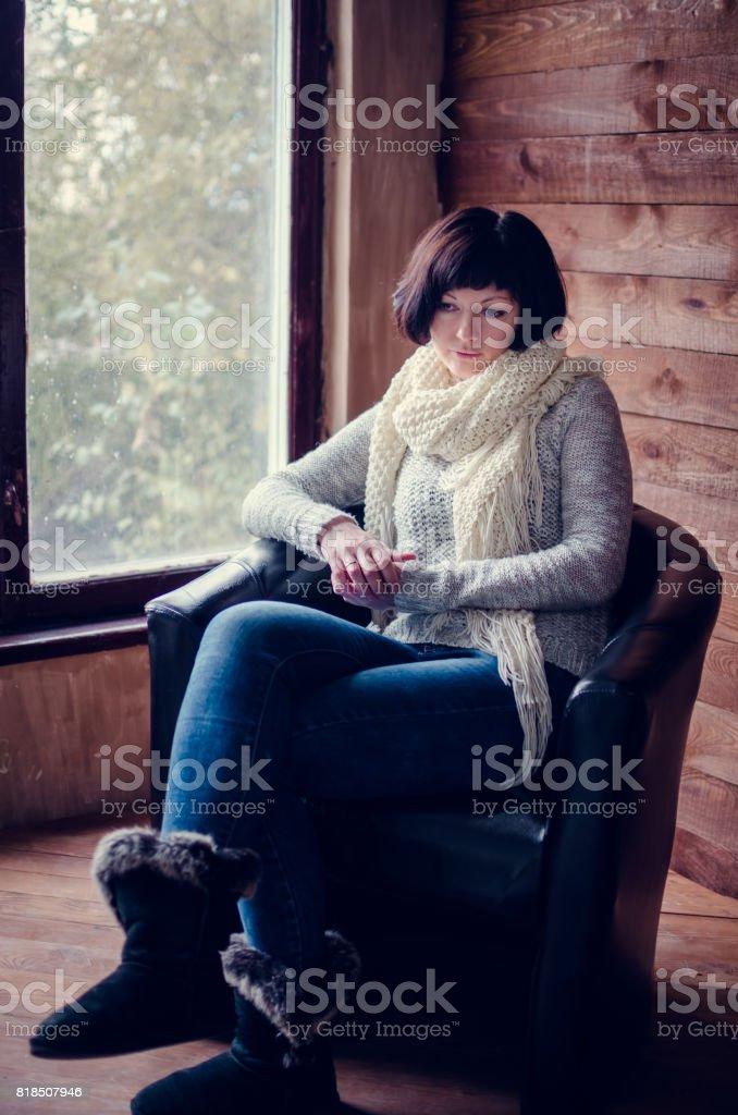 Beautiful woman sitting in an armchair stock photo