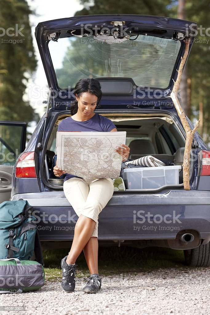 Beautiful woman sitting in car trunk with map royalty-free stock photo