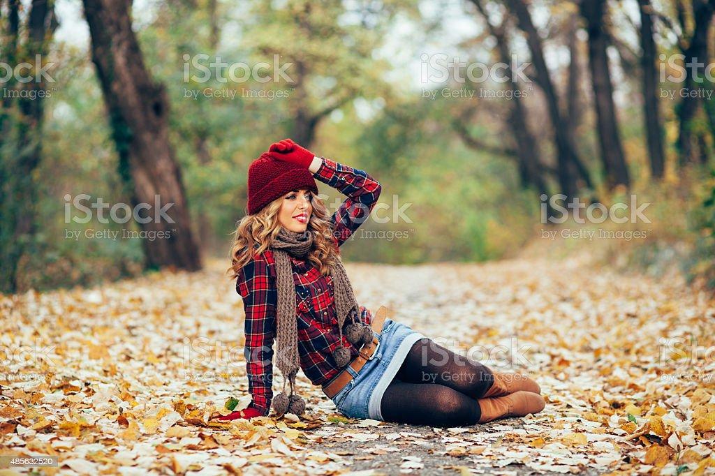 Beautiful woman sitting in fallen leaves stock photo