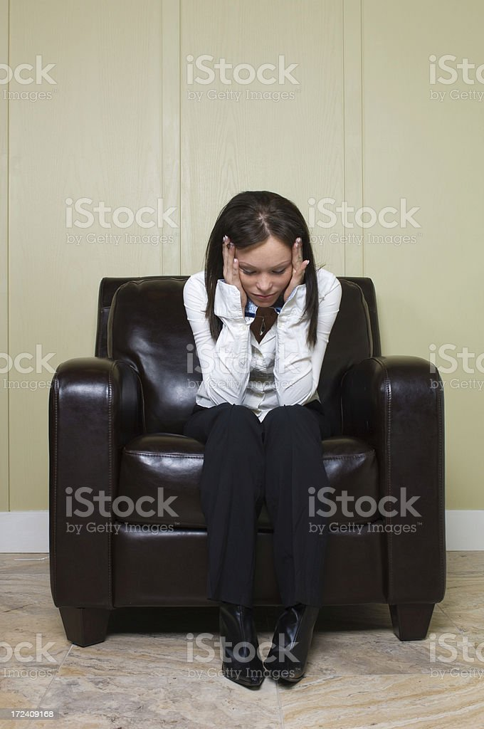 Beautiful woman sitting on a leather chair stock photo