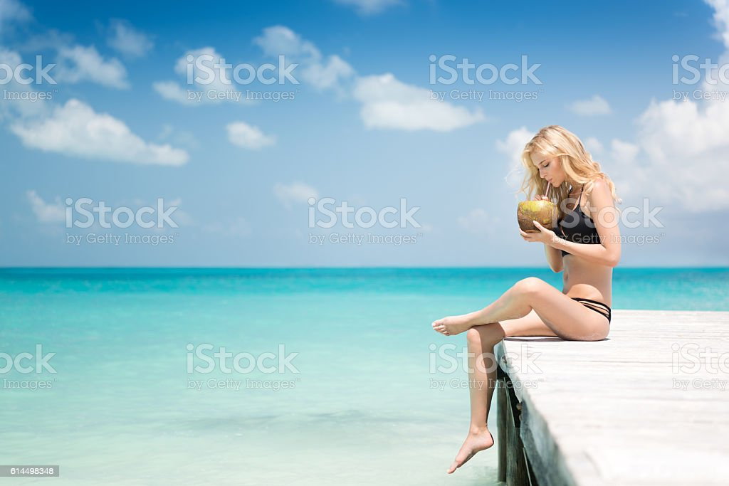 Beautiful woman sitting on a pier drinking a fresh Coconut stock photo
