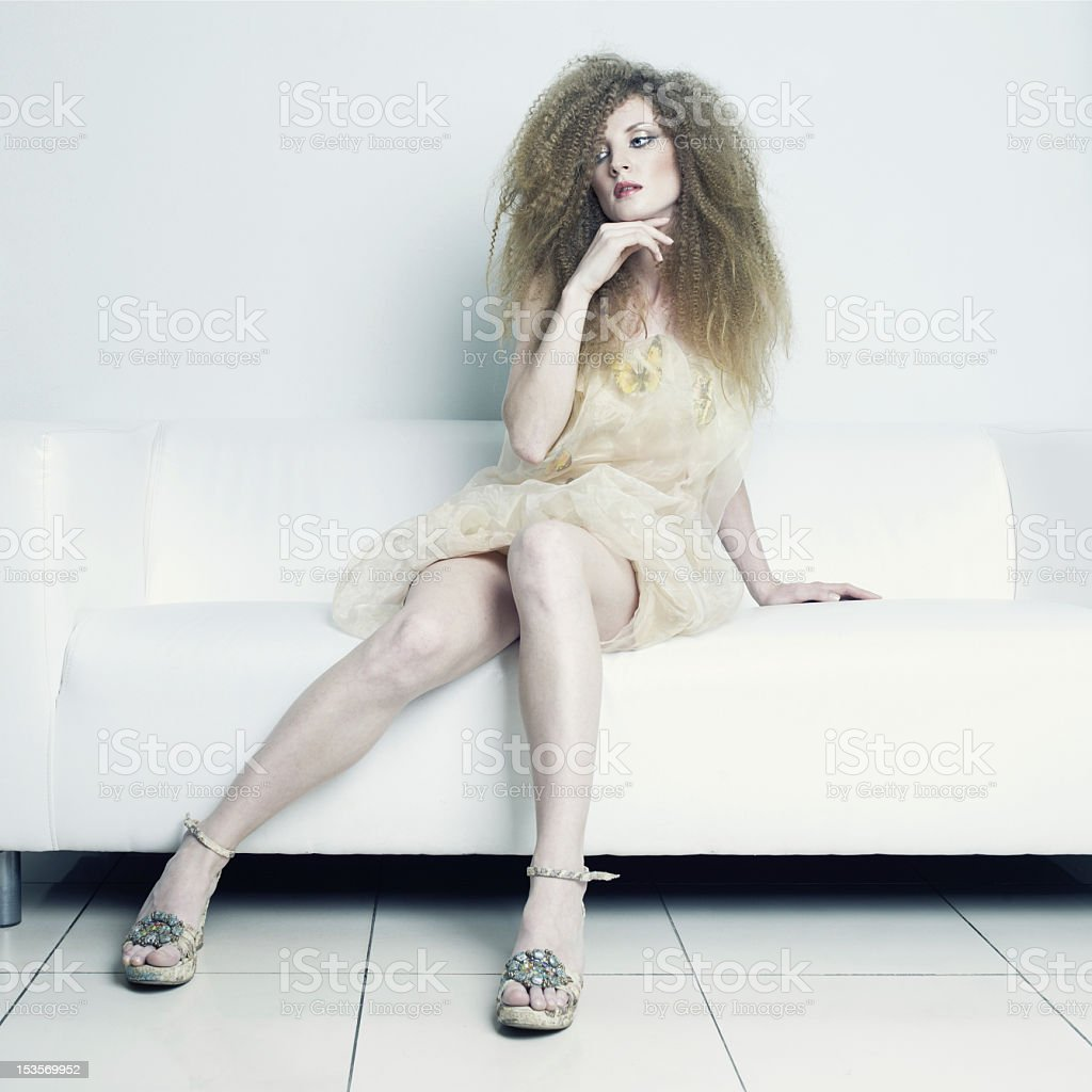 Beautiful woman sitting on a sofa royalty-free stock photo