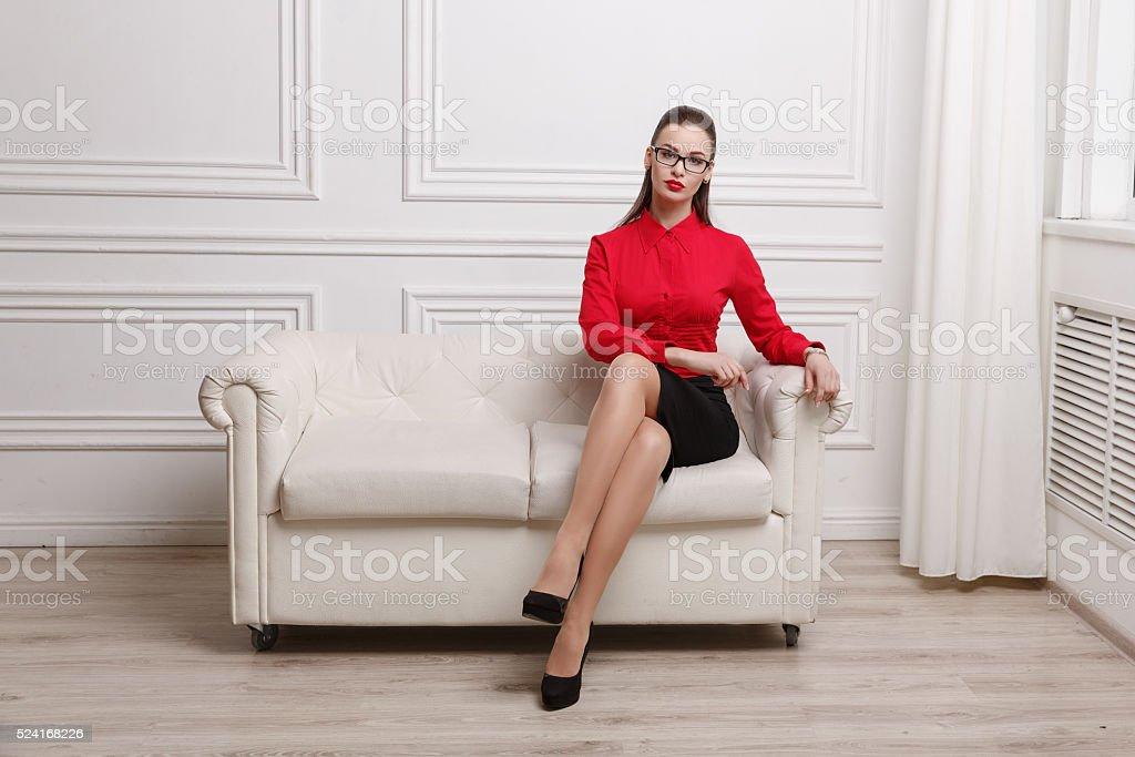 Beautiful woman sitting on a sofa stock photo
