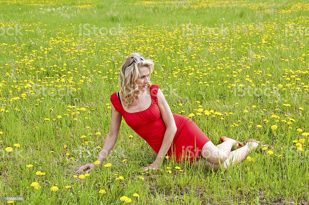 beautiful woman sitting on meadow stock photo
