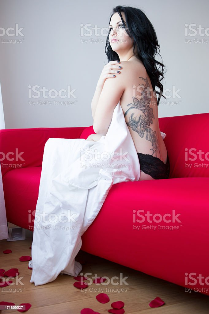 Beautiful woman sitting on red couch with rose petals royalty-free stock photo