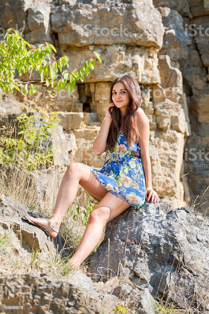 Beautiful woman sitting on rock stock photo