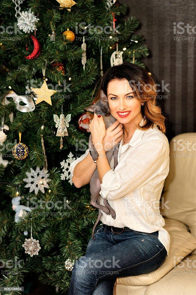 Beautiful woman sitting on the sofa near Christmas tree stock photo