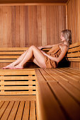 Beautiful woman sitting relaxed in a wooden sauna   brown towel