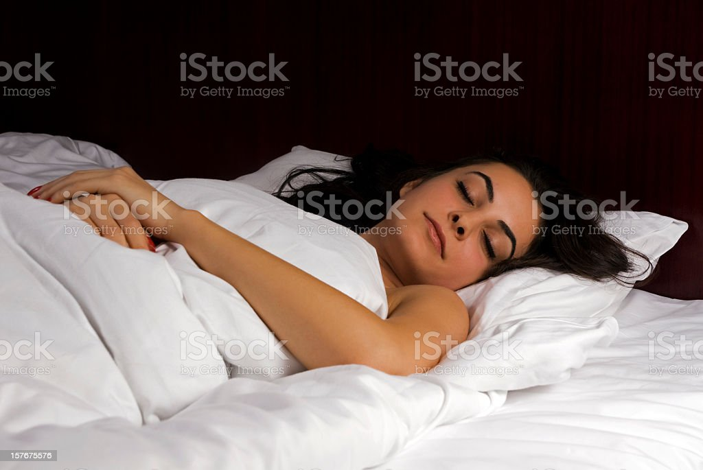 Beautiful woman sleeping in soft bed and fluffy quilt stock photo