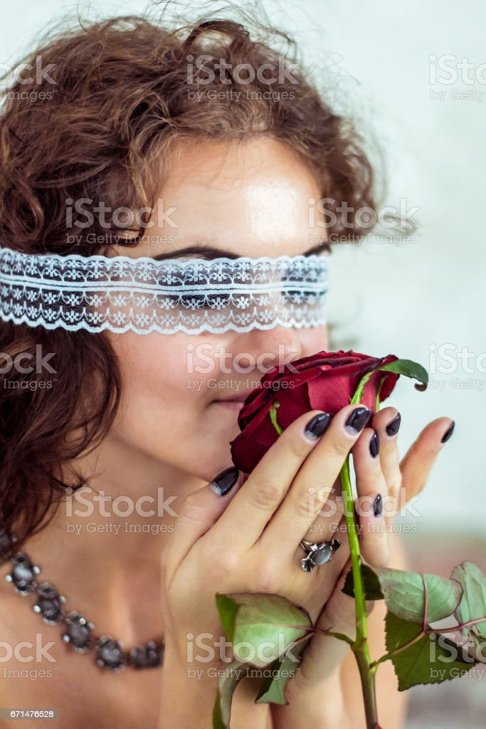 Beautiful woman smells red rose stock photo