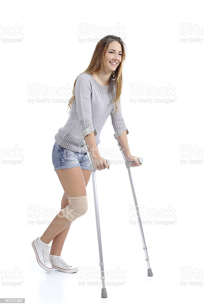 Beautiful woman smiling and hobbling with crutches stock photo