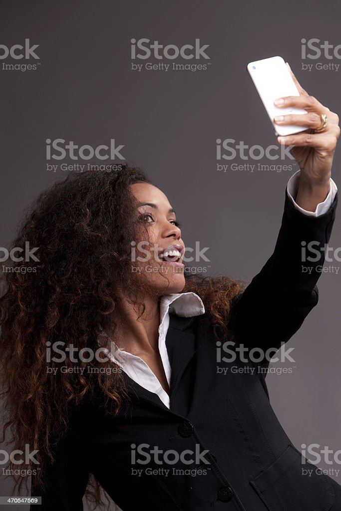 Beautiful woman smiling at her phone stock photo