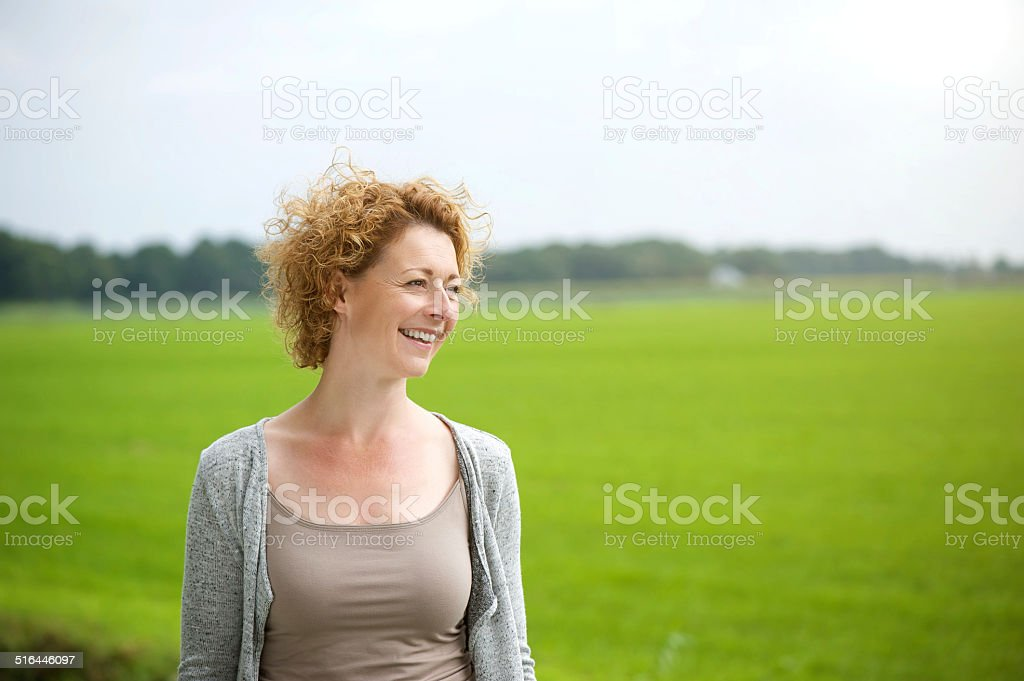 Beautiful woman smiling outdoors by green countryside stock photo