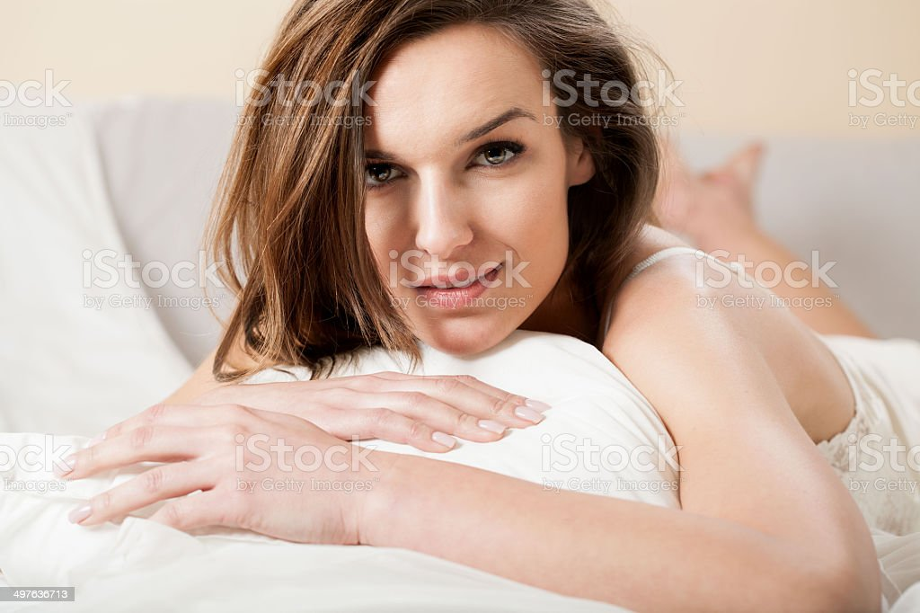 Beautiful woman smiling seductively in bed stock photo