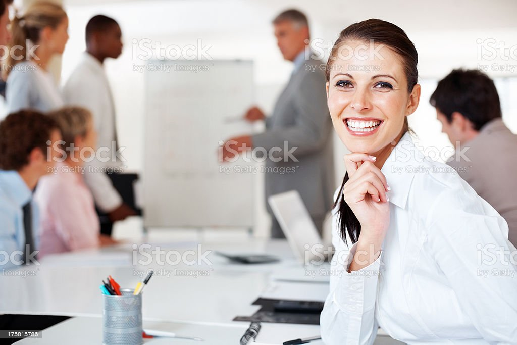 Beautiful woman smiling with team busy in presentation stock photo