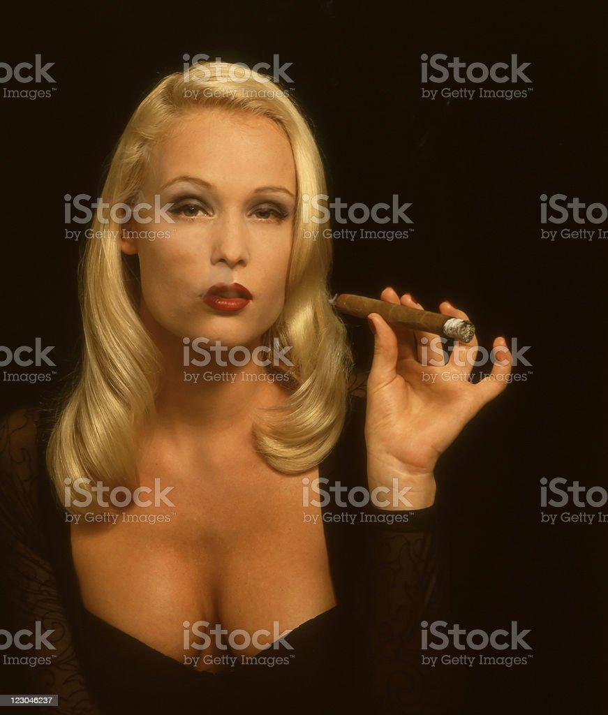 Beautiful woman smoking a cigar stock photo