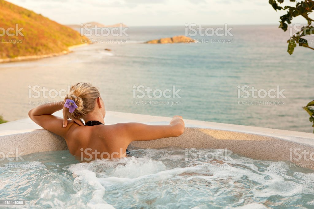 beautiful woman soaking in a jacuzzi at the Caribbean villa stock photo