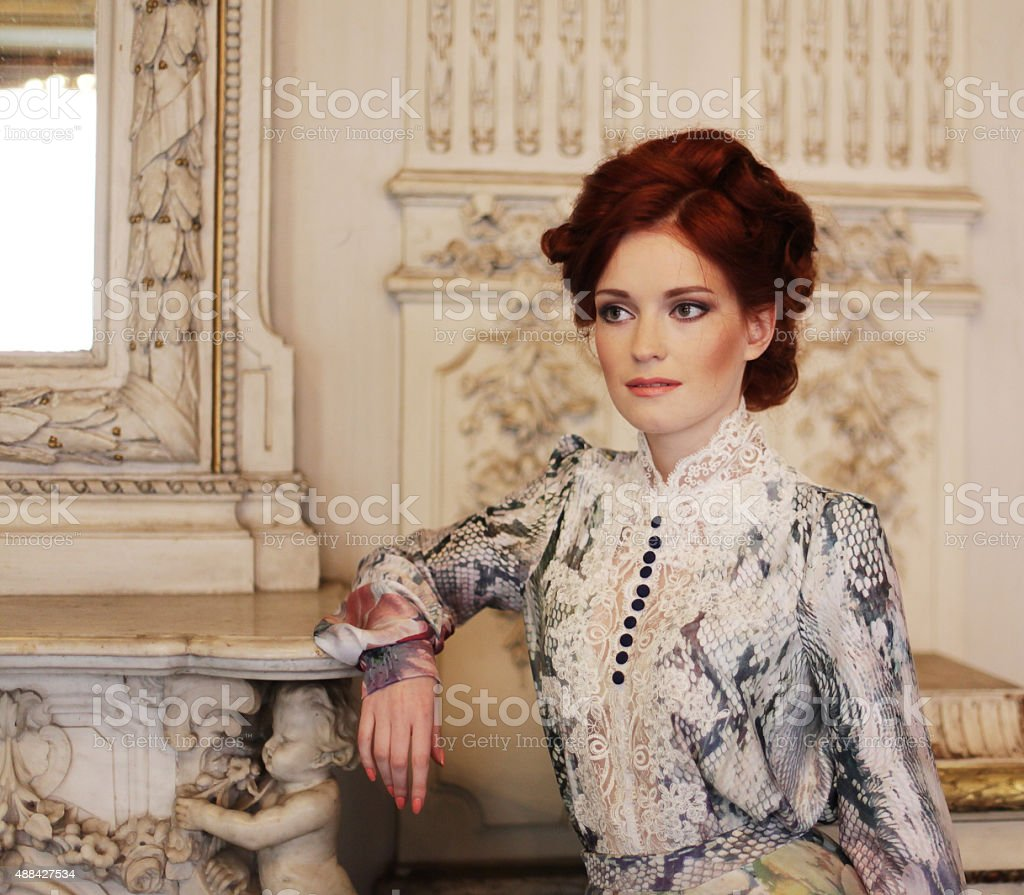 beautiful woman standing in the palace room. stock photo