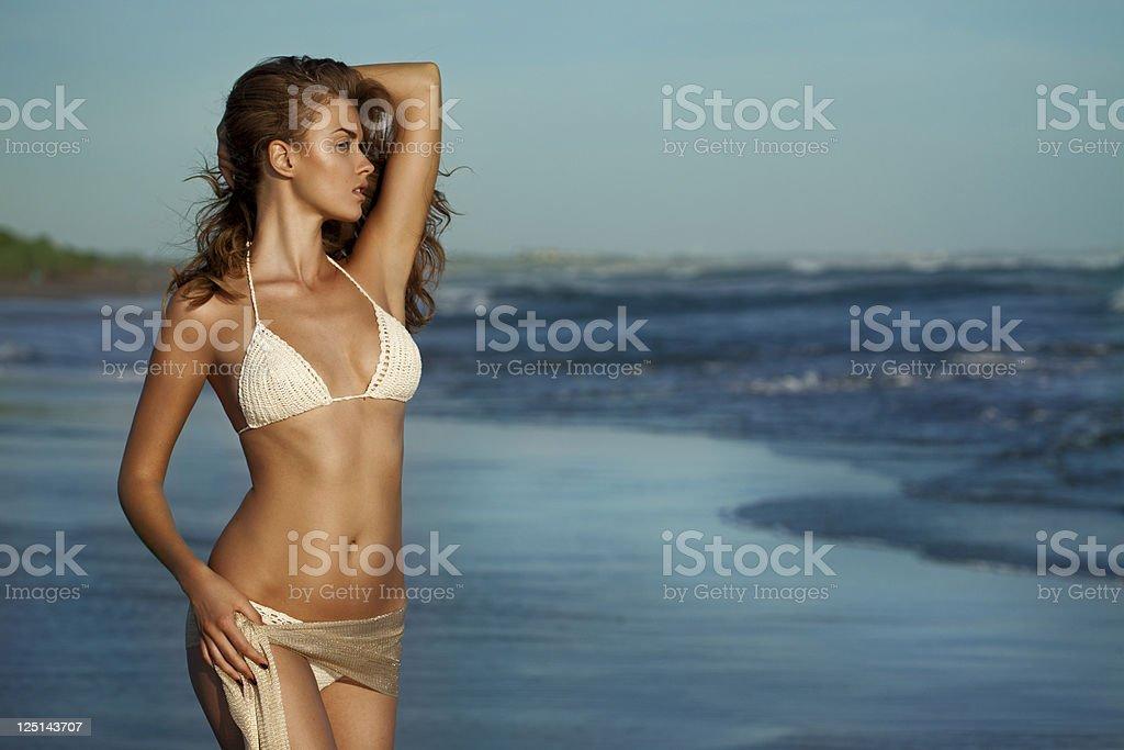 Beautiful woman standing on the beach stock photo