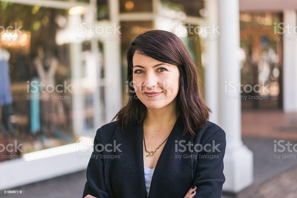 Beautiful woman standing outside shop stock photo